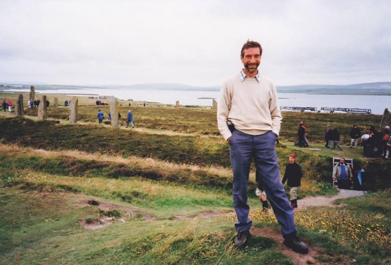 A man standing on a grassy mound with a large stone circle and the sea in the background