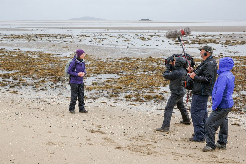 Photograph of blogger Karen Thorburn on a sand and seaweed beach in wet weather, being filmed by a filmcrew of three people