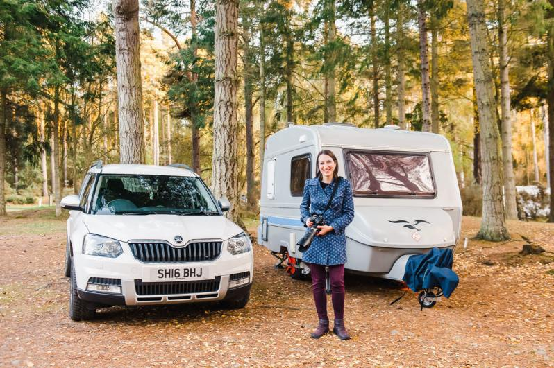 Blogger and photographer Karen Thorburn holding a camera and standing in front of a white car and grey caravan in a woodland