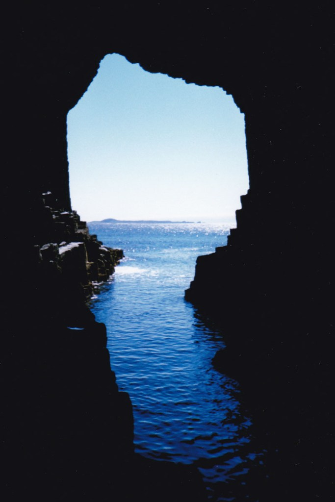 A view looking out of a large cave entrance, towards a blue sky and blue sea, and a small island in the distance