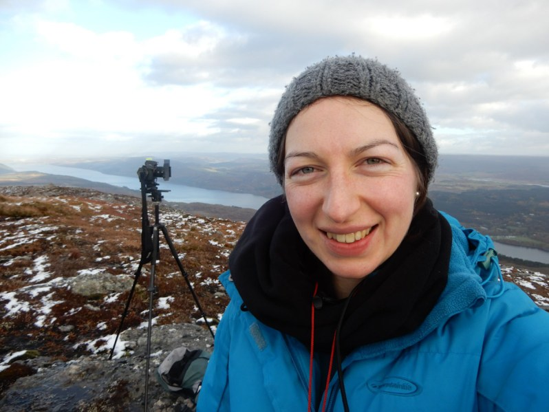 Close up photograph of a woman in a blue jacket and grey hat, with a camera and tripod set up behind her on a mountain top