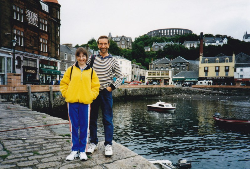 A father and teenage daughter in casual clothes in front of a harbour with shops, a distillery and a tower behind them