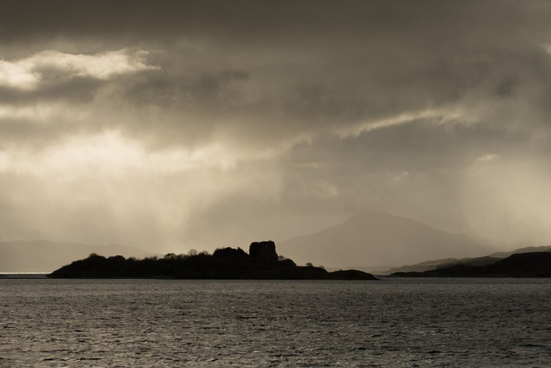 Rain clouds lit by the sun above small islets off the shore of the Isle of Lismore, with mountains in the distance