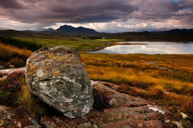 A landscape photograph of a large boulder in front rough grass, with a lake and mountains in the background