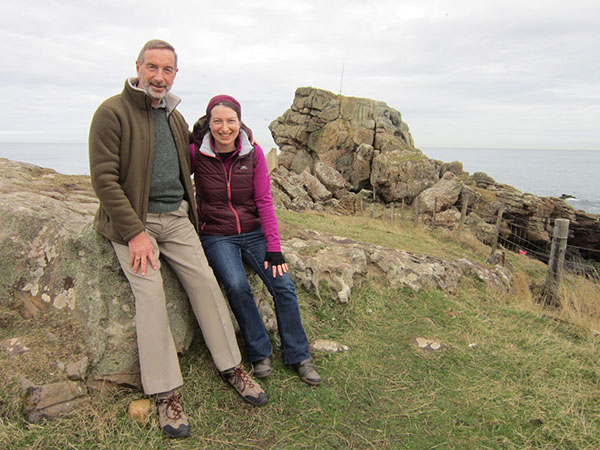 A father and adult daughter sitting side by side on a rock, with a large rock and the coast in the background