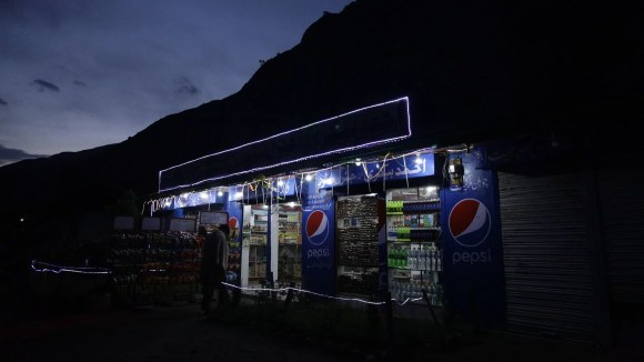 The fluorescent lights of a tea shop and grocery store light the Karakoram Highway. Photo by Diaa Hadid.