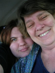 Two women smile at the camera. One is older, with short ash-blonde hair and a toothy smile. The other is younger, with a closed mouth smile and red hair. She rests her chin on her mother's shoulder, and it's clear she's holding the camera for both of them.