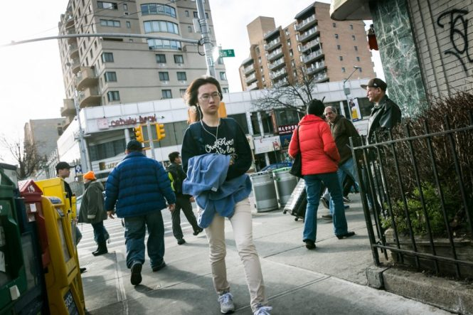 Woman with headphones walking in Flushing Queens street photography series