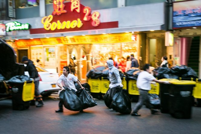 Restaurant workers hauling out trash in Flushing Queens street photography series