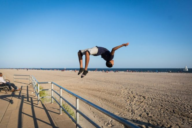 Coney Island street photography of a kid doing a back flip