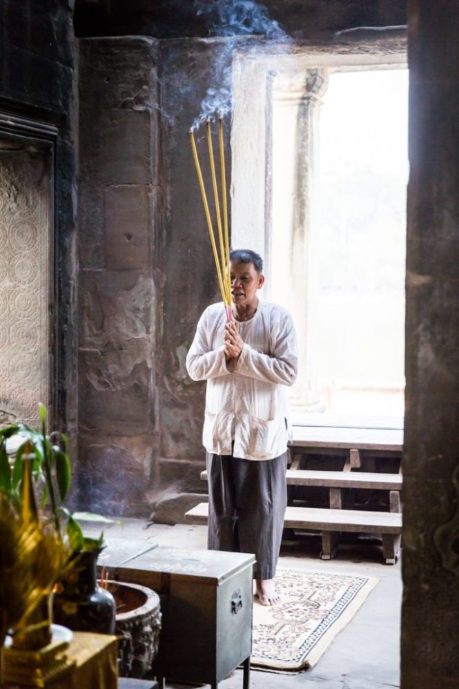 Man with long incense sticks for an Angkor Wat temple guide