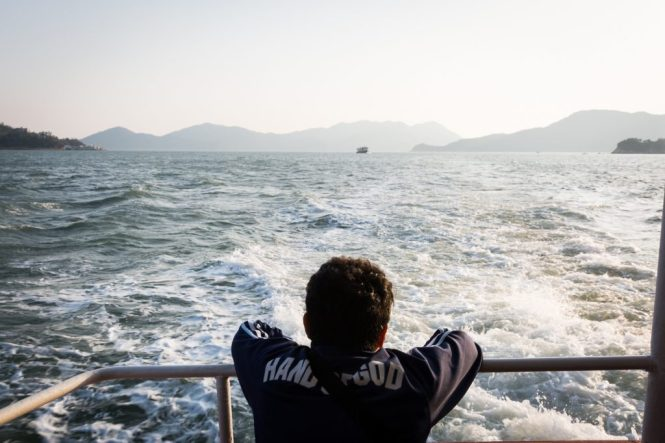 Man traveling on ferry for a Hong Kong travel guide article