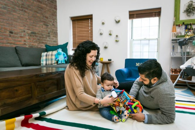 Parents reading with child for an article on indoor baby portrait tips