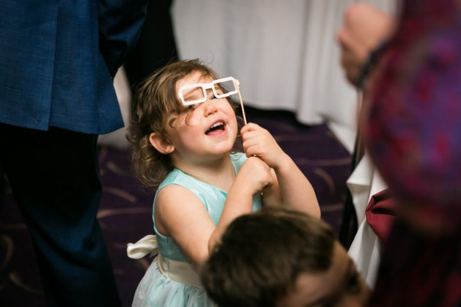 Little girl playing with photo booth prop at a Glen Terrace wedding