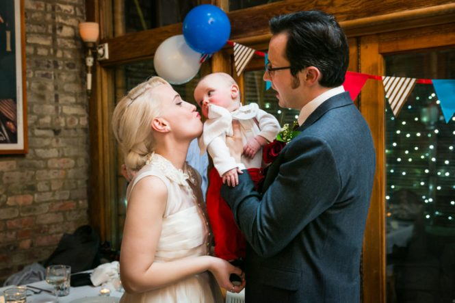 Bride, groom, and baby at a Scottadito wedding