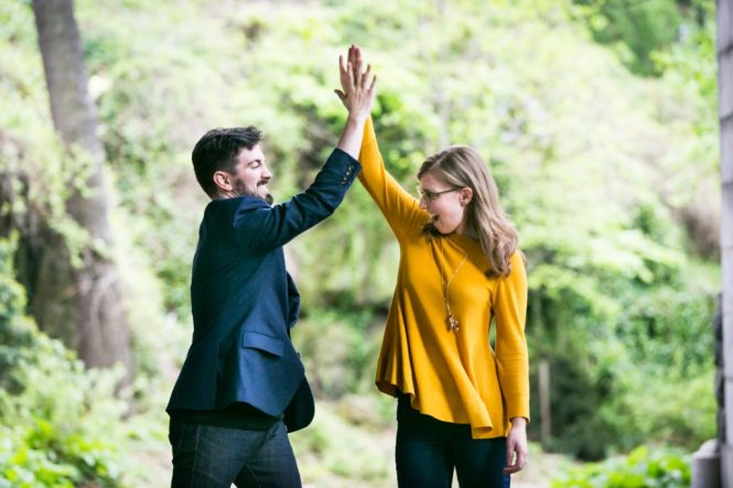 High-fiving couple at a Fort Tryon Park engagement portrait
