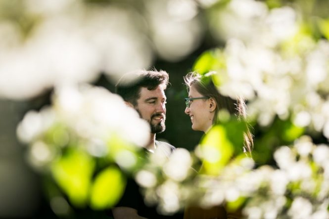 Couple through the leaves at a Fort Tryon Park engagement portrait