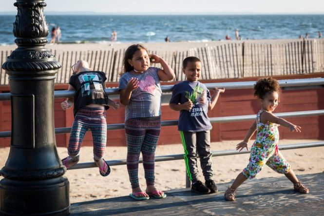 Kids posing for a photo on the Coney Island boardwalk