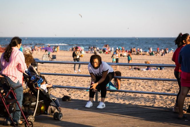 Woman sitting on the Coney Island boardwalk railing