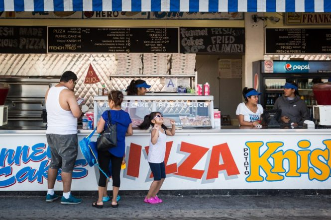 Kid with sunglasses dancing in front of a Coney Island hot dog stand