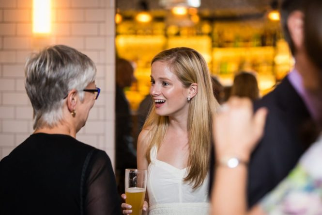 Guests at a rehearsal dinner for an article on details your wedding photographer needs to know