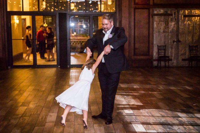 Groom and flower girl dancing at a 26 Bridge wedding
