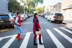 Couple walking in a crosswalk dressed as Spiderman and Supergirl for a Comic Con engagement shoot