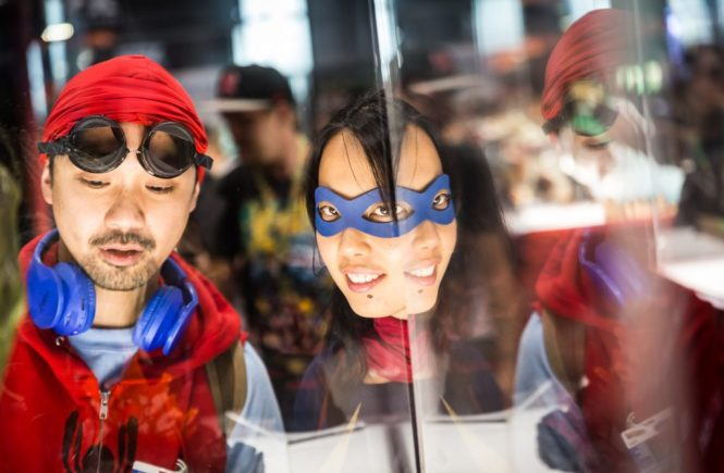 Couple in a mirror dressed as Spiderman and Supergirl for a Comic Con engagement shoot