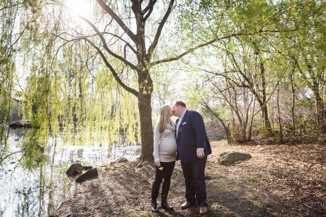 Parents kissing in park for an article on the best family portrait poses