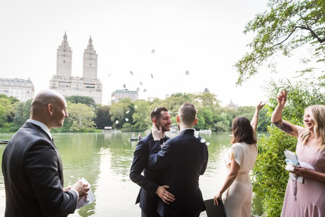 Wedding party throwing rose petals for an article entitled, 'Do you need a permit to get married in Central Park?'