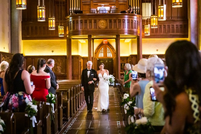 Bride and father walking down aisle for an article on Bronx Zoo wedding venue updates