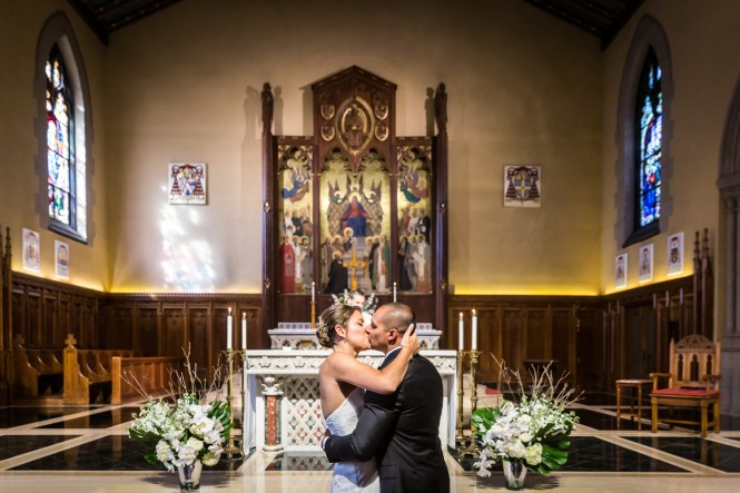 Bride and groom kissing during wedding ceremony for an article on Bronx Zoo wedding venue updates