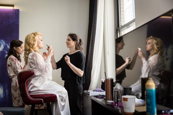 Bride having makeup done at a Central Park Conservatory Garden wedding