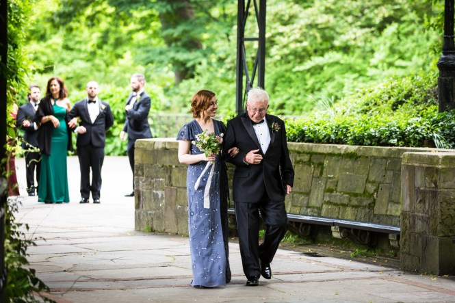 Bridesmaid and grandfather walking down aisle at a Central Park Conservatory Garden wedding