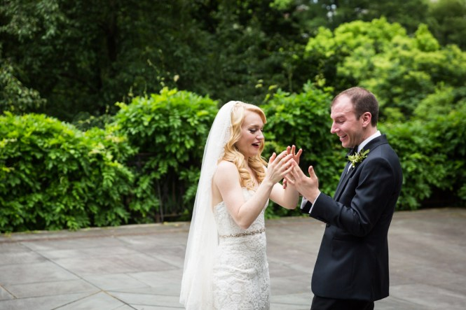 Bride and groom looking at rings at a Central Park Conservatory Garden wedding