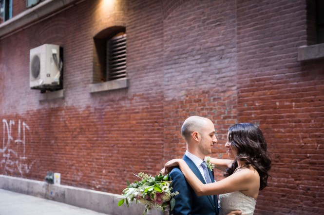 Bride and groom hugging in brick alleyway for an article on non-floral centerpiece ideas