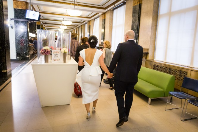 Bride and groom walking into City Clerk's Office