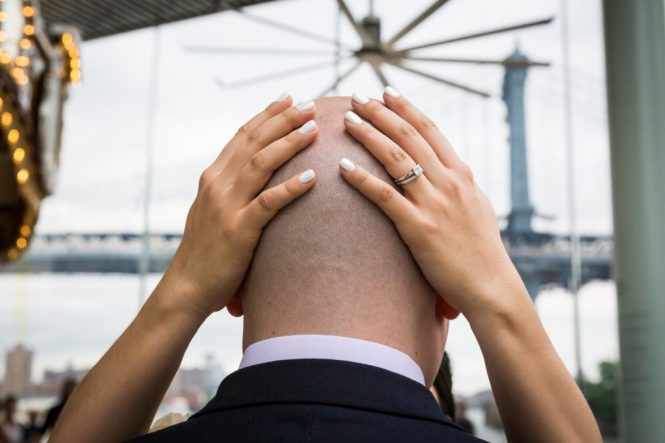 Bride's hands on groom's bald head
