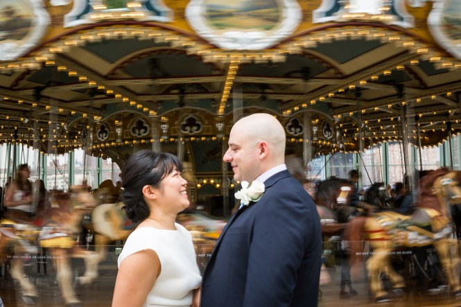 Bride and groom in front of spinning carousel