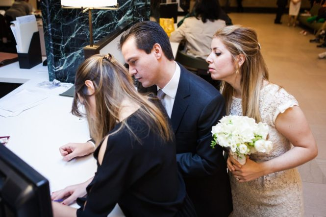 Filling out paperwork at a Manhattan Marriage Bureau wedding, by NYC wedding photojournalist, Kelly Williams