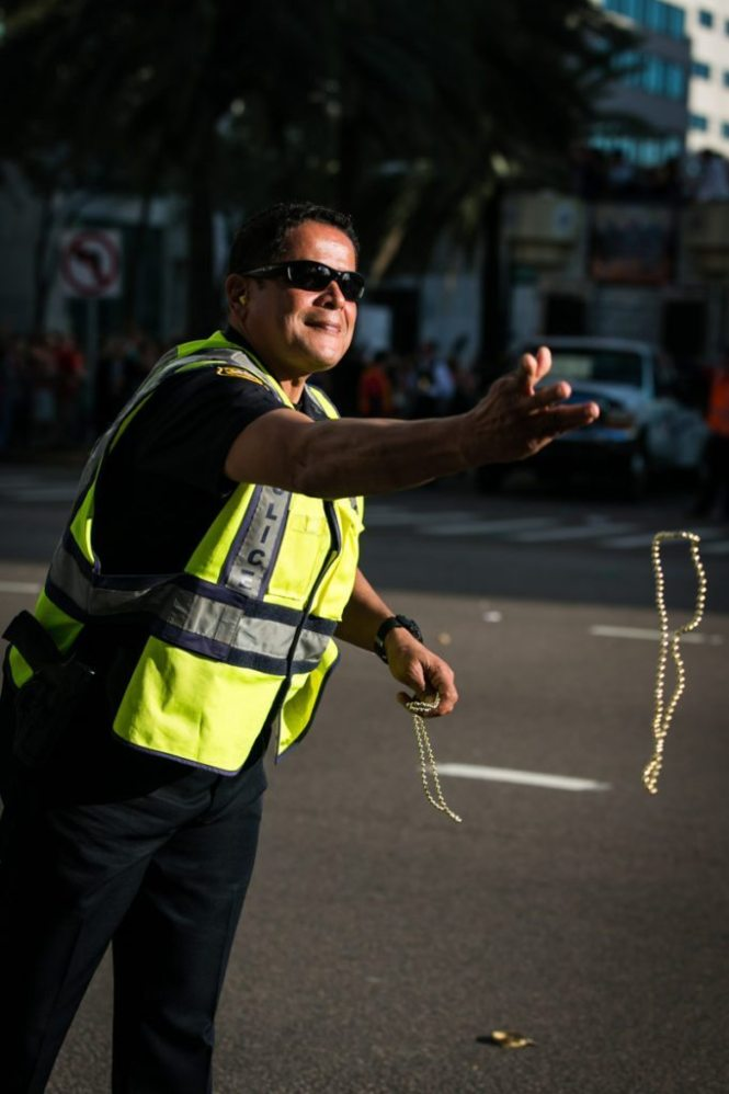 A friendly cop distributes beads, by NYC photojouralist, Kelly Williams.