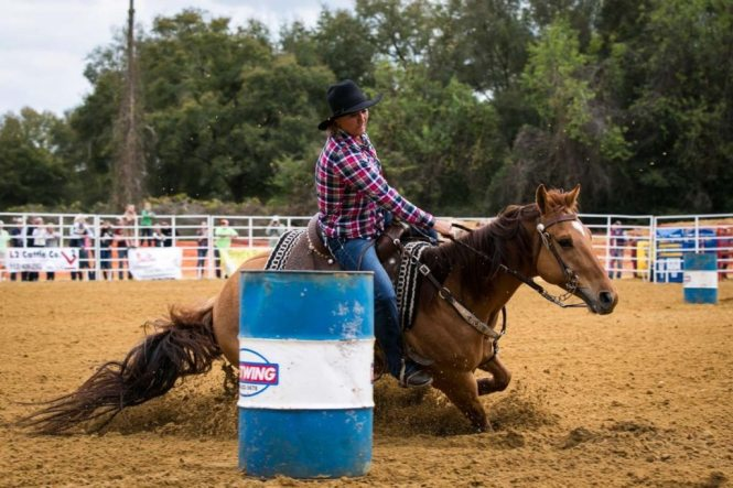 Barrel racing at the county fair championship rodeo, by NYC photojournalist, Kelly Williams
