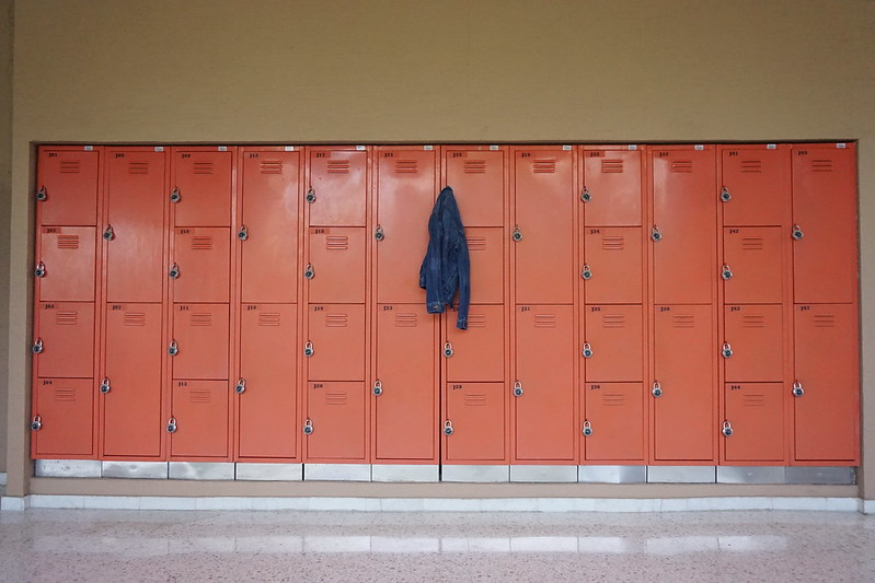 A picture of a lone jacket hanging from a row of lockers.