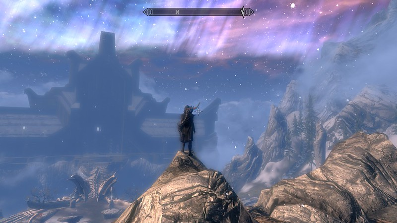 Screenshot from the game Skyrim with character on a high rock overlooking a night sky and a building in the distance