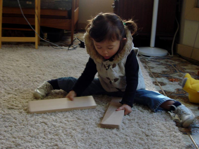 A young child playing with blocks while doing the splits.