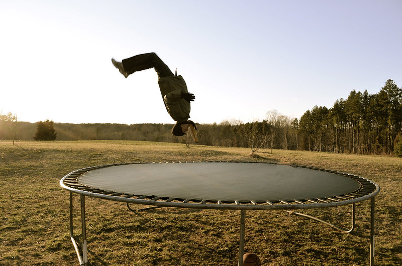A person doing a flip on a trampoline in a field.