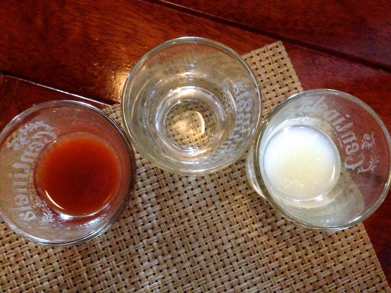 "Picture of three shot glasses. ""Lunch with Ken and his family, introduced to this style of shots, with Don Julio tequila in the middle, followed bib lime (right) and sangria (left) -- the colors of the Mexican flag."""