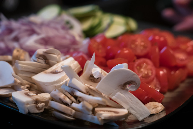 Sliced mushrooms, onions, cherry tomatoes prepared for pizzas.