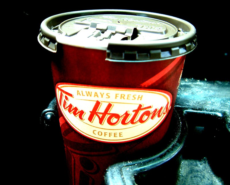 Image in a car cup holder of a Tim Hortons takeout coffee cup.