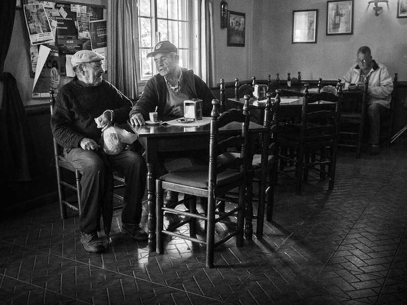 Black and white photo of what appears to be older people in conversation in a restaurant.